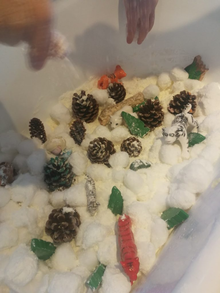 Sensory bin with fake snow for tiger habitat